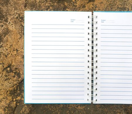 White open notebook on rock background.