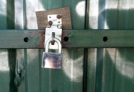 A padlock on an iron green door.