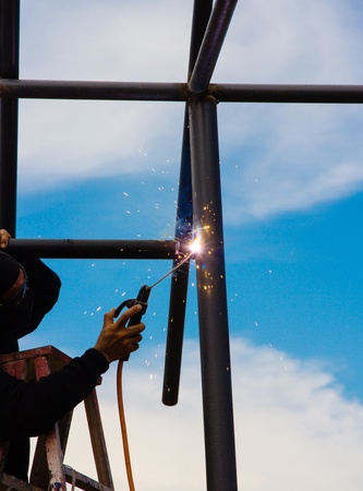 Welder works sparkle cutting metal photo