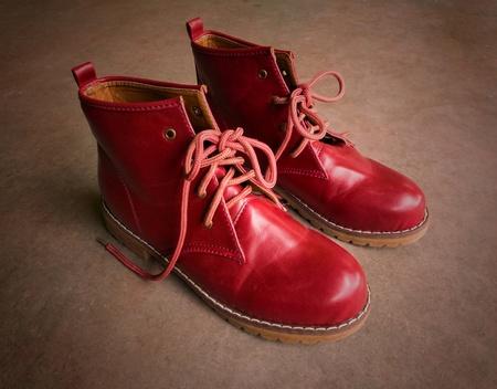 untied: Botas rojas y los cordones desatados sobre fondo marr�n.
