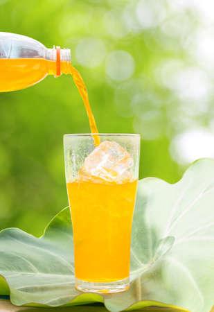 verre jus orange: Verser le jus d'orange de tomber dans un verre sur les feuilles, en plein air Banque d'images
