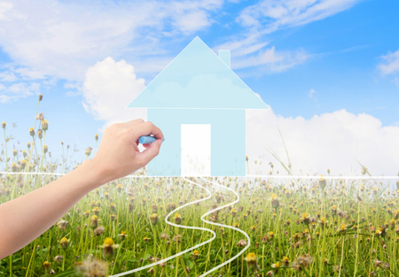 Hand with a chalk draws a house on grass with sky. Stock Photo