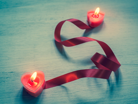 Two burning heart shaped candles with red ribbon.