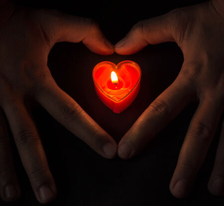 burning heart in heart hands.