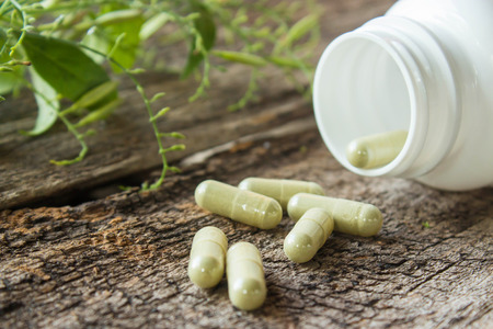 Herb capsule with green herbal leaf and bottle Stockfoto