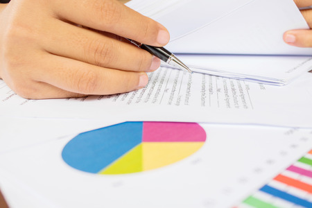 Close-up of female hand with document and graph Stock Photo