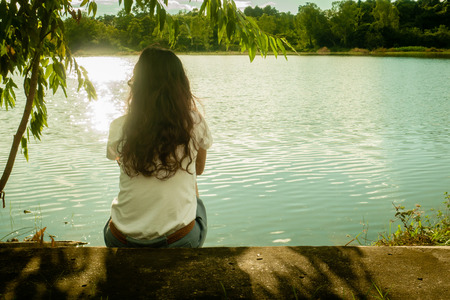 lost lake: woman is thinking beside the lake. Stock Photo