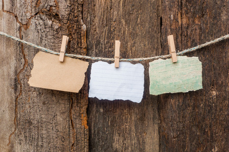blank note hanging on old wooden background