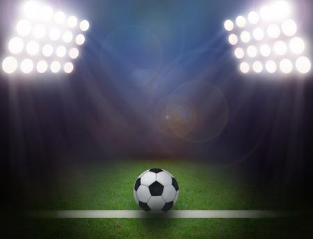 Soccer ball on green stadium, arena in night illuminated bright spotlights.