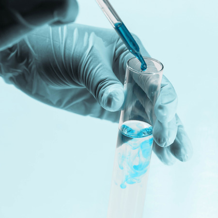 Scientist hand holding a Test tubes close up on blue background,Laboratory research.