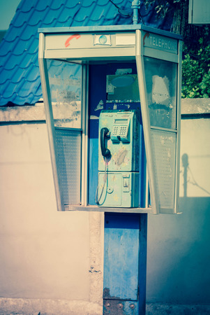 defaced: Aged and vintage photo of old public phone booth