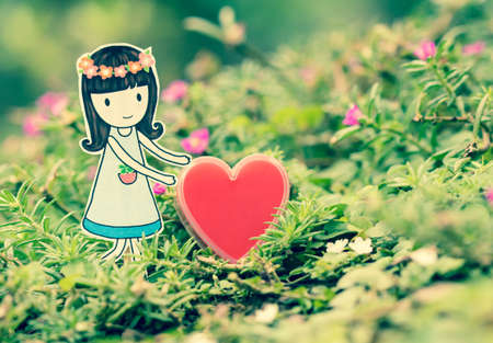 day dreaming: young woman with red heart in the nature