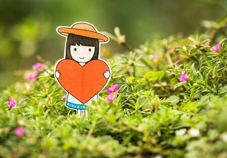 day dreaming: young woman holding red heart in the nature