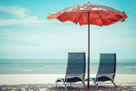 strandstoel: Beach stoel en parasol op zand strand.