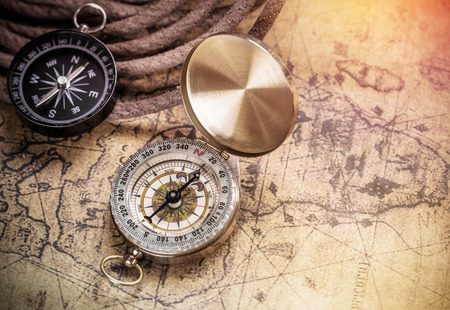 history: compass on vintage map with accessory to the Adventure.