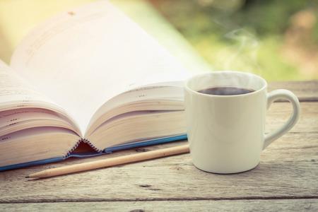 tomando café: Taza de café con libros sobre la mesa.