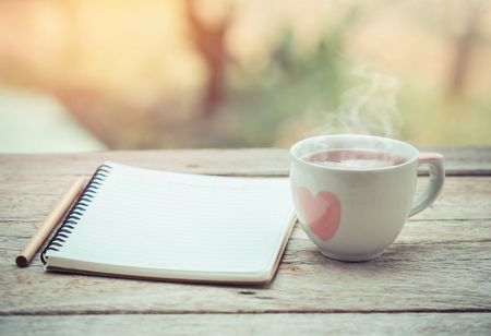 cup of tea with notebook on the table. Stock Photo