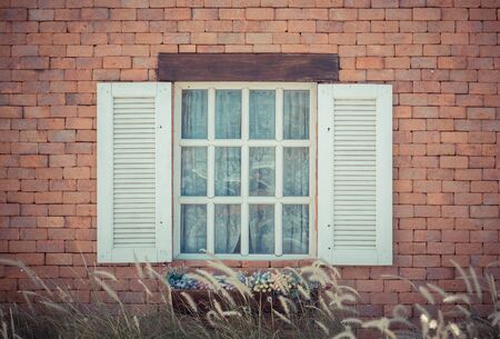 Open vintage window with flower on brick wall