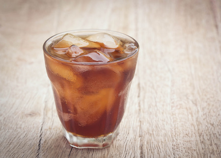 carbonation: glass of cola with ice cubes on wood