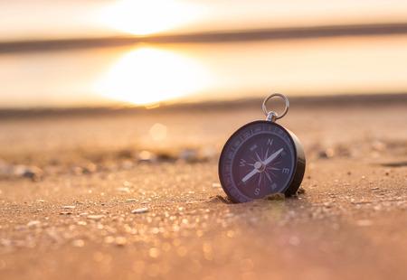 compass on the beach with sunrise Foto de archivo