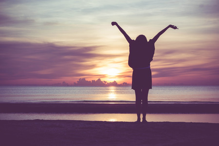 winning: Woman spreading hands with joy and inspiration at sunrise.