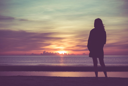 Young woman standing on the beach in sea and looking to sunrise.