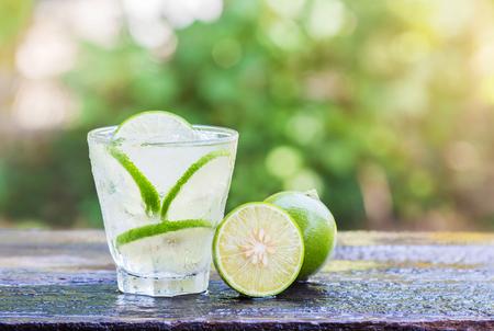 Cold fresh lemonade with lemon on wooden table.