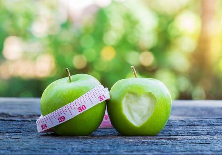 salud y deporte: manzana verde fresca y cinta de medición con forma de corazón sobre la mesa de madera.