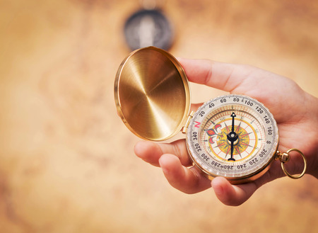Child hand holding a compass on the map background.