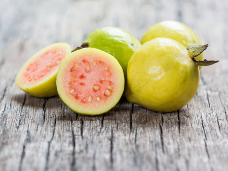 Fresh guava fruit on wooden table. Banco de Imagens