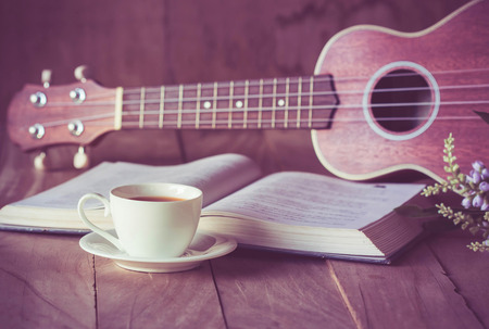 Cup of tea on table with ukulele and book.