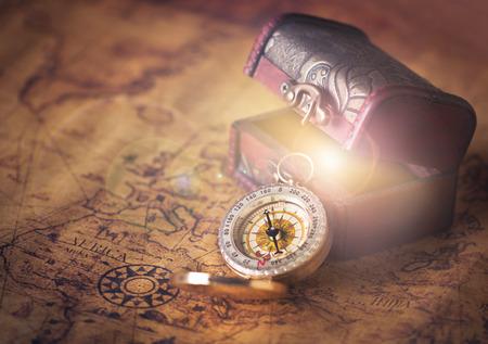 mapa del tesoro: br�jula en el mapa de cosecha con cofre del tesoro Foto de archivo