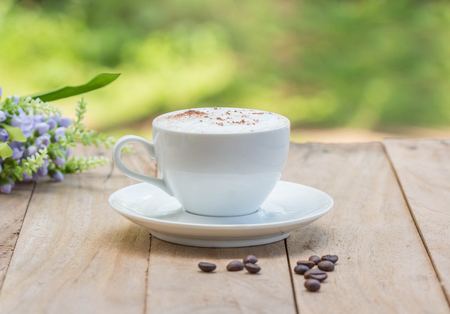 coffee cup and beans on wooden table in the morning. Stock Photo