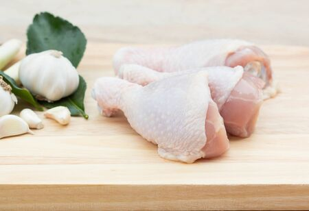 Raw Chicken legs on wooden table.