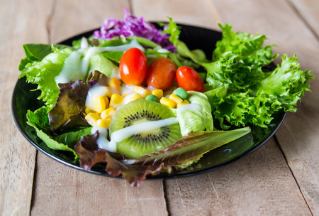 Fresh healthy salad in plate on wooden table.