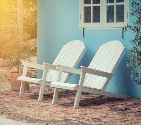 front house: White wood chairs in front of house. Stock Photo