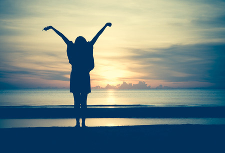 sunrise ocean: Woman spreading hands with joy and inspiration at sunrise.