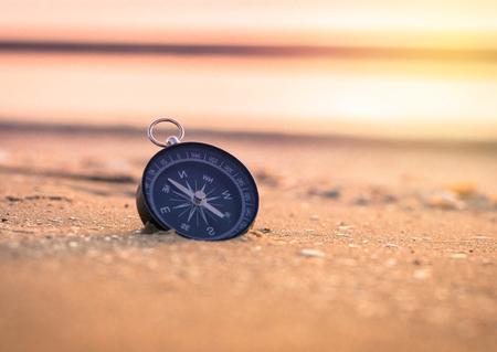 brujula: brújula en la playa con la salida del sol