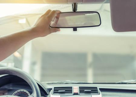 Hand adjusting rear view mirror.
