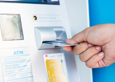 automatic transaction machine: female hand inserts credit card into the ATM and withdraws money n very shallow focus. Foto de archivo