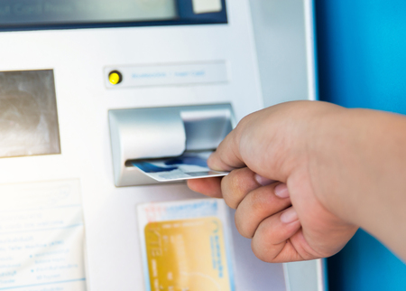 automatic transaction machine: female hand inserts credit card into the ATM and withdraws money in very shallow focus.