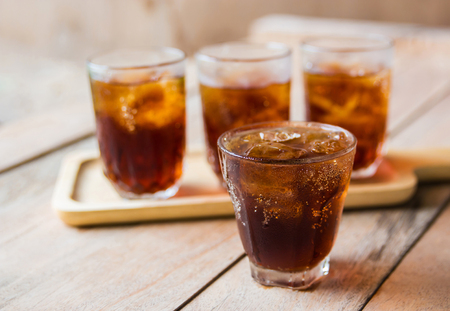 carbonation: glass of cola with ice cubes on table.