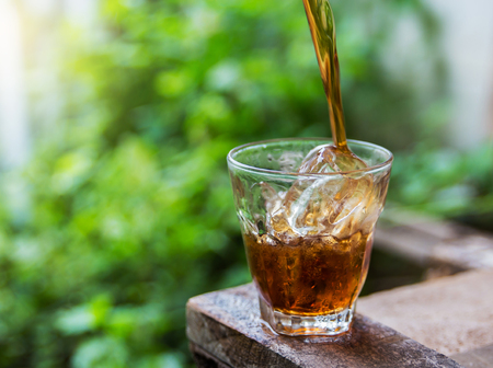 carbonation: Cola drink is poured into a glass with ice. Stock Photo