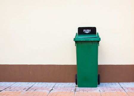 segregate: Green Recycling Bin on the floor and concrete wall.