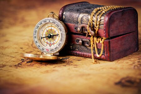 Old compass on vintage map with treasure Chest