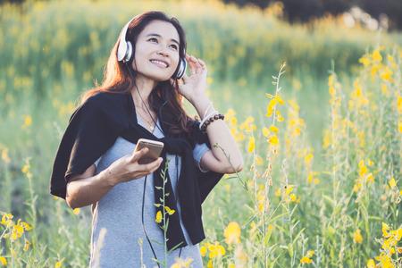 Beautiful happy asian woman enjoying in yellow field,Happy Woman Enjoying Nature.  Stock Photo