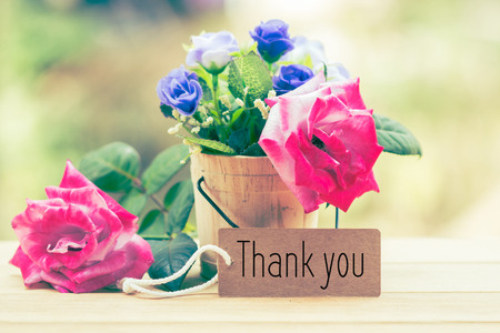 Writing thank you on card with rose on desk.