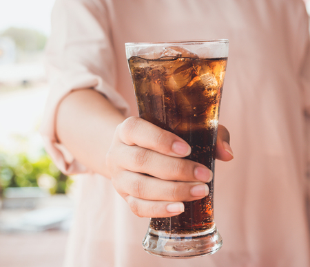 carbonation: Woman hand giving glass of cola.Glass of cola ,Soft drinks with ice. Stock Photo