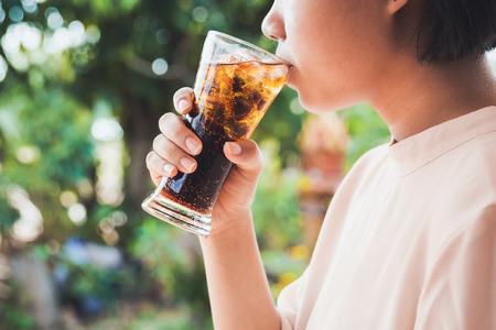 얼음 콜라의 유리를 마시는 여자.