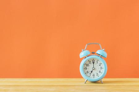 Blue alarm clock on Orange background,Minimal creative style.